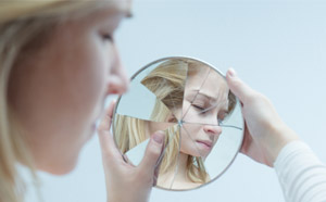 Woman looking away from broken mirror